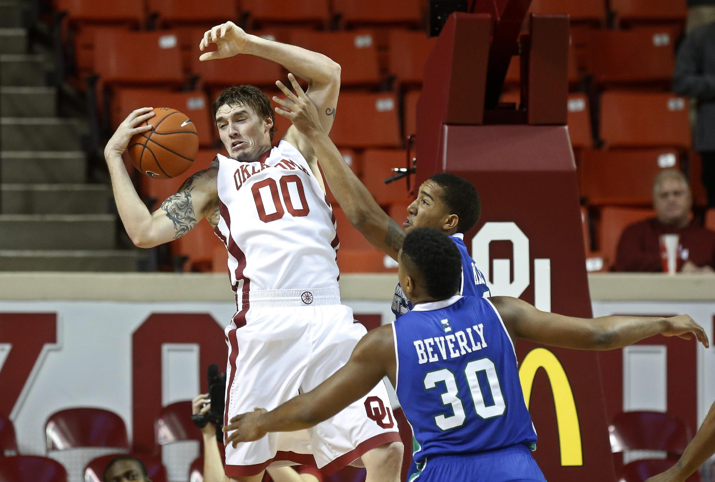 Oklahoma's Ryan Spangler (00) grabs a rebound in front of Texas A&M Corpus Christi forward Jeff Beverly (30) and forward Zane Knowles, rear, during the first half of an NCAA college basketball game in Norman, Okla., Thursday, Dec. 5, 2013