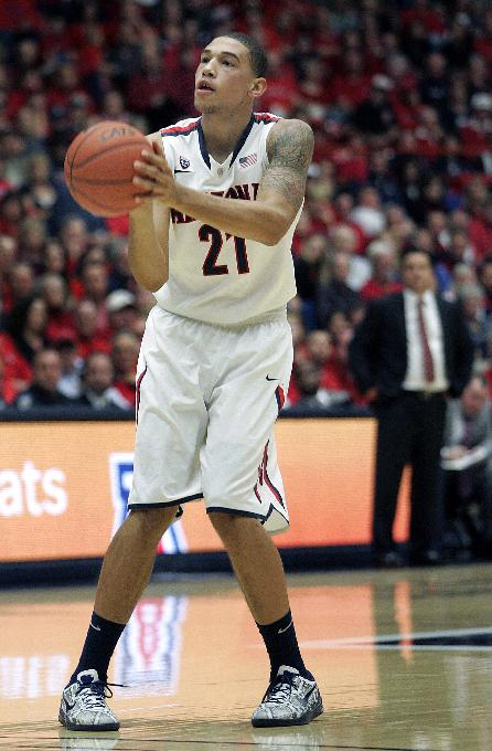 Arizona's Brandon Ashley (21) shoots for two of his 15 points against New Mexico State as Arizona's head coach Sean Miller watches in the background in the first half of an NCAA college basketball game on Wednesday, Dec. 11, 2013 in Tucson, Ariz