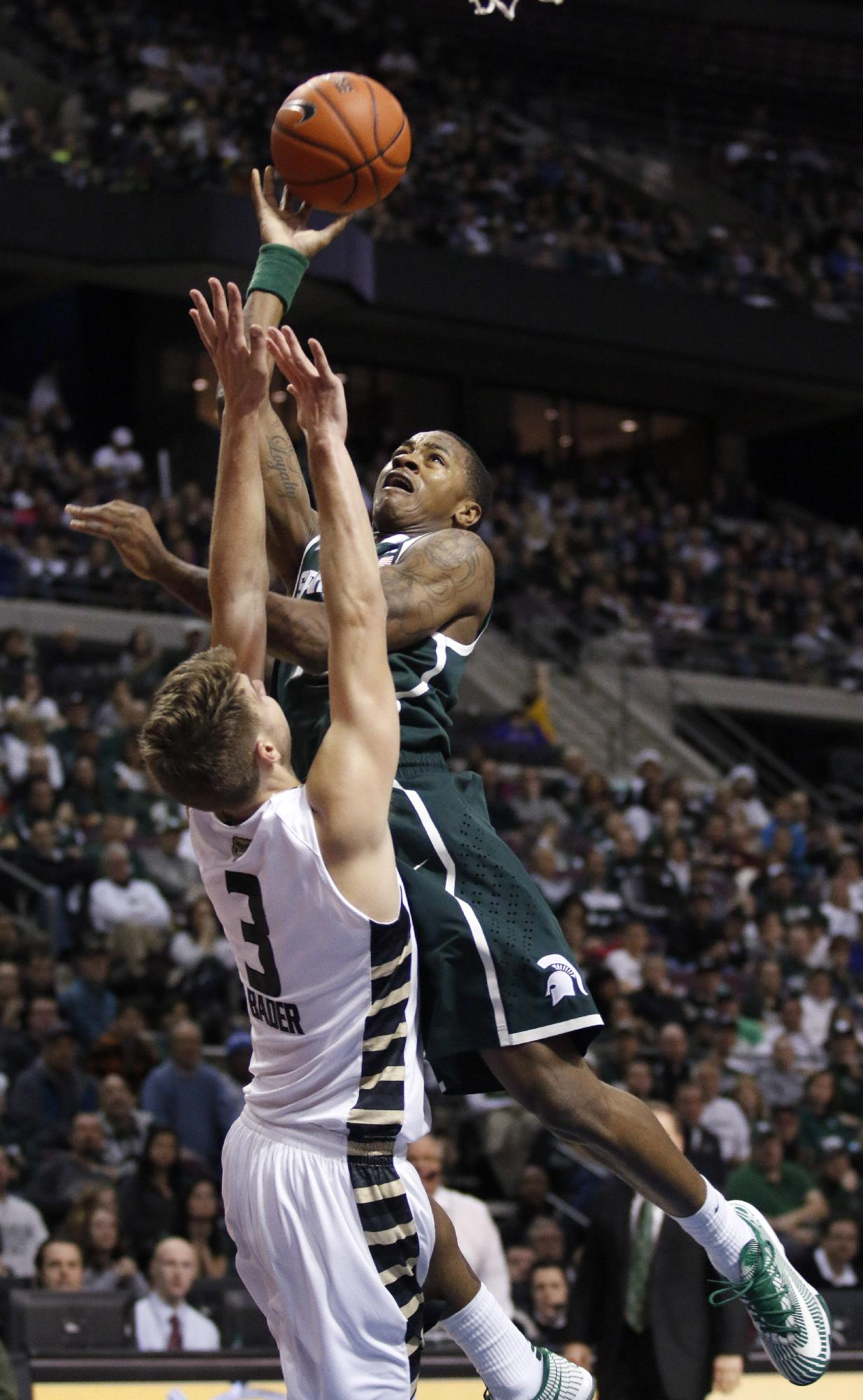 Michigan State's Keith Appling, right, puts up a shoot against Oakland's Travis Bader (3) during the second half of an NCAA college basketball game, Saturday, Dec. 14, 2013, in Auburn Hills, Mich. Appling led Michigan State with 21 points in a 67-63 win