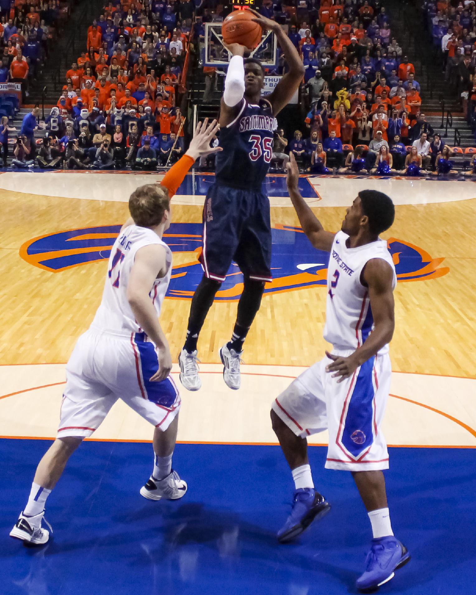 Saint Mary's James Walker III, center, shoots over Boise State's Jeff Elorriaga, left, and Derrick Marks, right, during the first half of an NCAA college basketball game in Boise, Idaho, Saturday, Dec. 14, 2013. Saint Mary's defeated Boise State 82-74