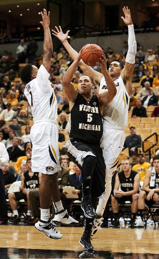 Western Michigan's David Brown, center, shoots between Missouri's Jordan Clarkson, right, Wes Clark, left, during the second half of an NCAA college basketball game Sunday, Dec. 15, 2013, in Columbia, Mo. Missouri won 66-60