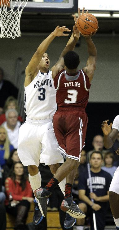 Villanova's Josh Hart, left, blocks a shot by Rider's Jimmie Taylor in the first half of an NCAA college basketball game, Saturday, Dec. 21, 2013, in Villanova, Pa