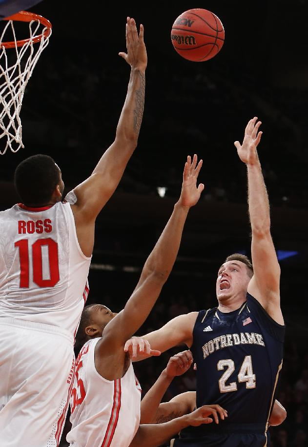 Ohio State's LaQuinton Ross (10) defends a shot by Notre Dame's Pat Connaughton (24) during the first half of an NCAA college basketball game Saturday, Dec. 21, 2013, in New York. Ohio State won 64-61