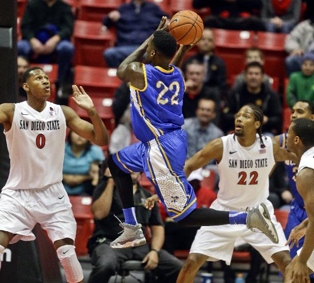 McNeese State guard Ledrick Eackles, center, drives to the basket as San Diego State center Skylar Spencer, left, and Josh Davis are near during the first half of an NCAA college basketball game in San Diego, Saturday, Dec. 21, 2013
