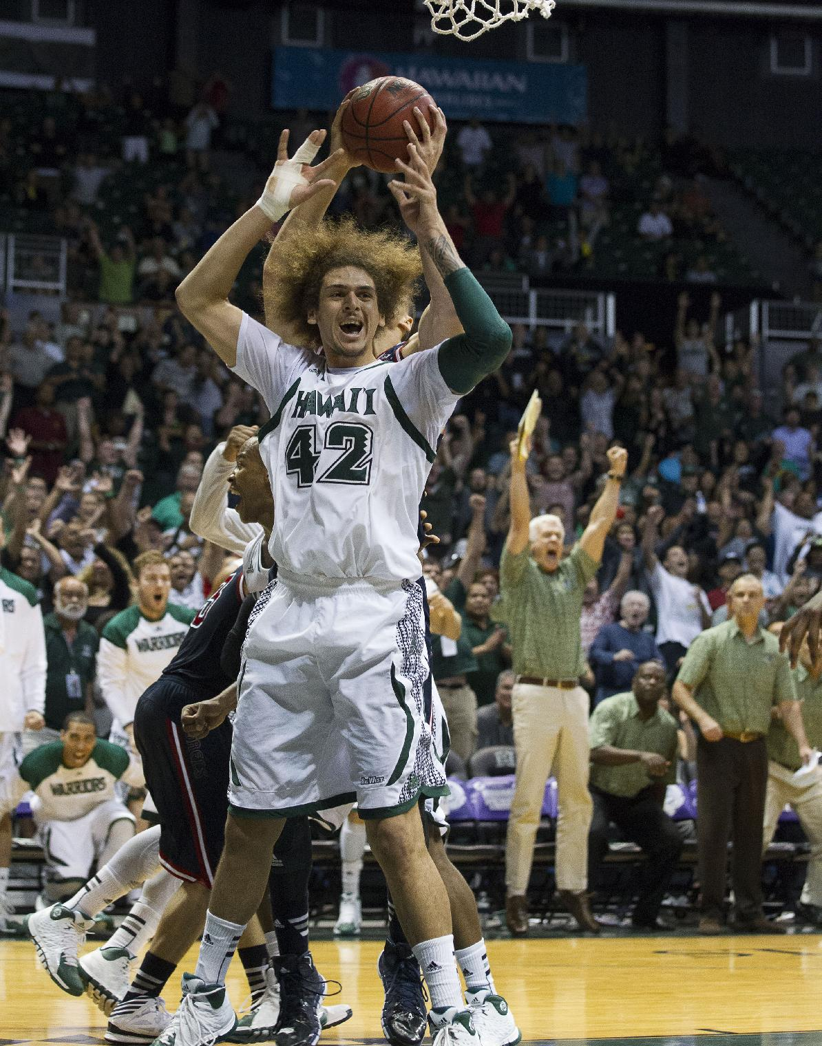 Hawaii forward Isaac Fotu (42) and the Hawaii bench react after Hawaii's Christian Standhardinger makes the game winning shot in the second half of an NCAA college basketball game at the Diamond Head Classic Monday, Dec. 23, 2013, in Honolulu. Hawaii beat Saint Mary's 76-74