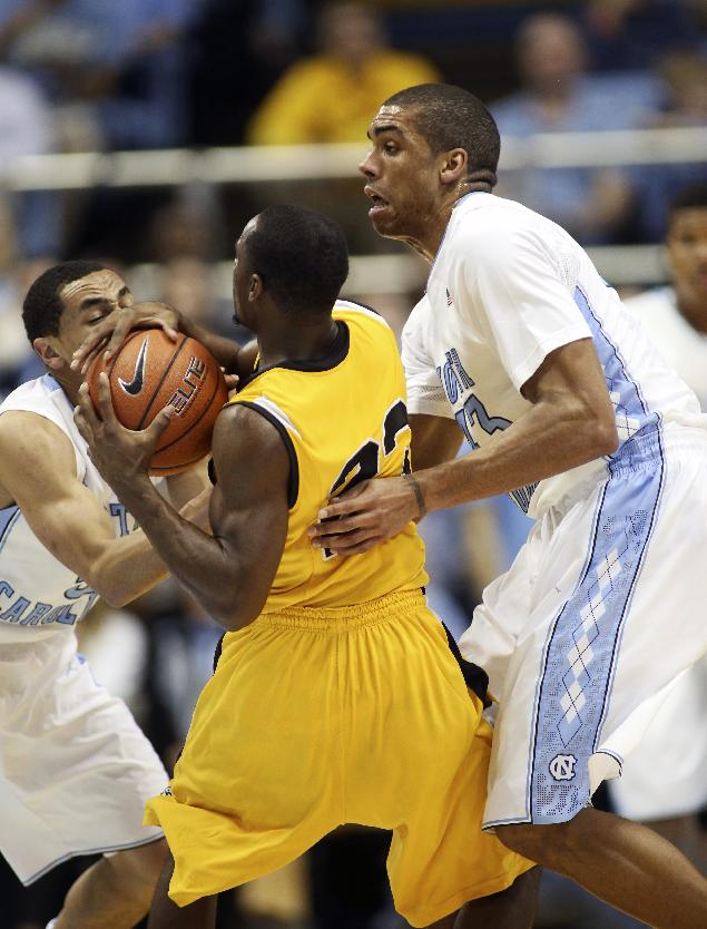 Northern Kentucky's Todd Johnson, center, gets wrapped up by North Carolina's Marcus Paige, left, and James Michael McAdoo, right, during the first half of an NCAA college basketball game in Chapel Hill, N.C. Friday, Dec. 27, 2013