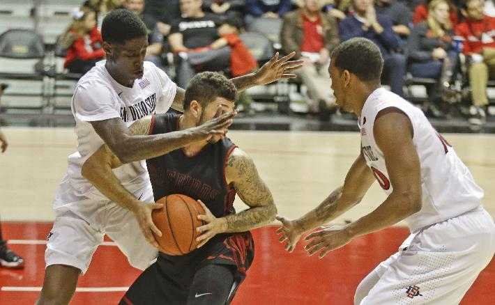 Saint Katherine guard Dante Miller, center, is trapped by San Diego State's Dwayne Polee, left, and Aqeel Quinn during the first half of an NCAA college basketball game on Friday, Dec. 27, 2013, in San Diego