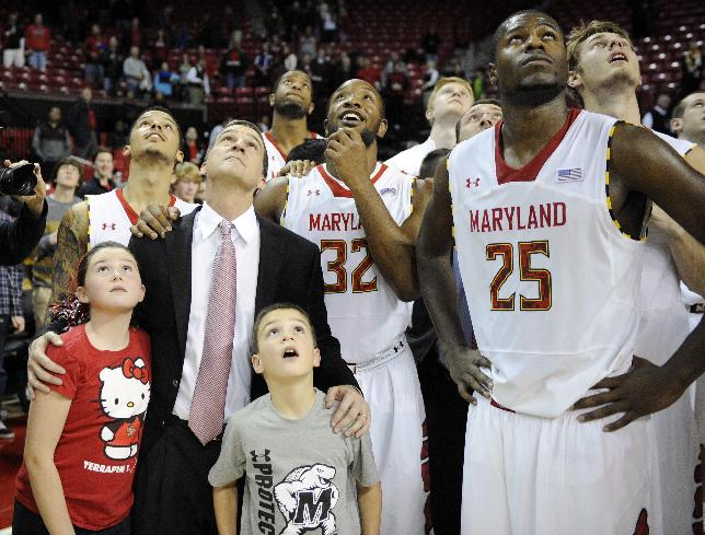 Maryland head coach Mark Turgeon, with tie, watches a video on the scoreboard with daughter Ella, bottom left, and son Leo, third from lower left, along with Maryland guard Seth Allen, top left, Dez Wells (32) and Jonathan Graham (25) after Maryland beat Tulsa 85-74 for Turgeon's 300th career win in an NCAA college basketball game, Sunday, Dec. 29, 2013, in College Park, Md