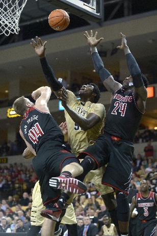 Central Florida forward Shaphon Blair, center, battles for a rebound between Louisville forward Stephan Van Treese (44) and Montrezl Harrell (24) during the first half of an NCAA college basketball game in Orlando, Fla., Tuesday, Dec. 31, 2013