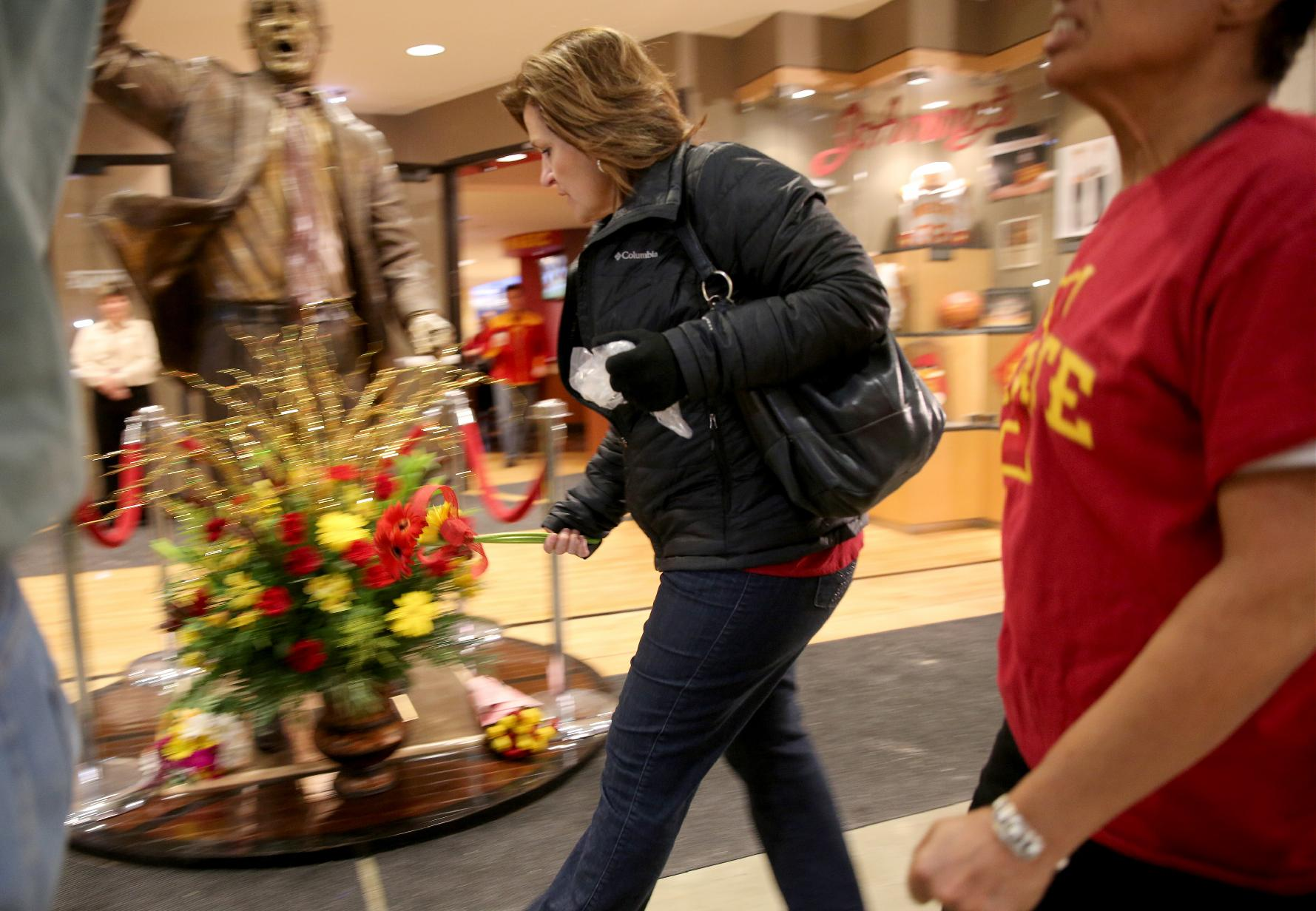 A fan stop drops off flowers at the statue of former Iowa State coach Johnny Orr before towa State's NCAA college basketball game against Northern Illinois at Hilton Coliseum in Ames, Iowa, Tuesday, Dec. 31, 2013. Orr, 86, who also coached at Michigan, has died, Iowa State confirmed Tuesday