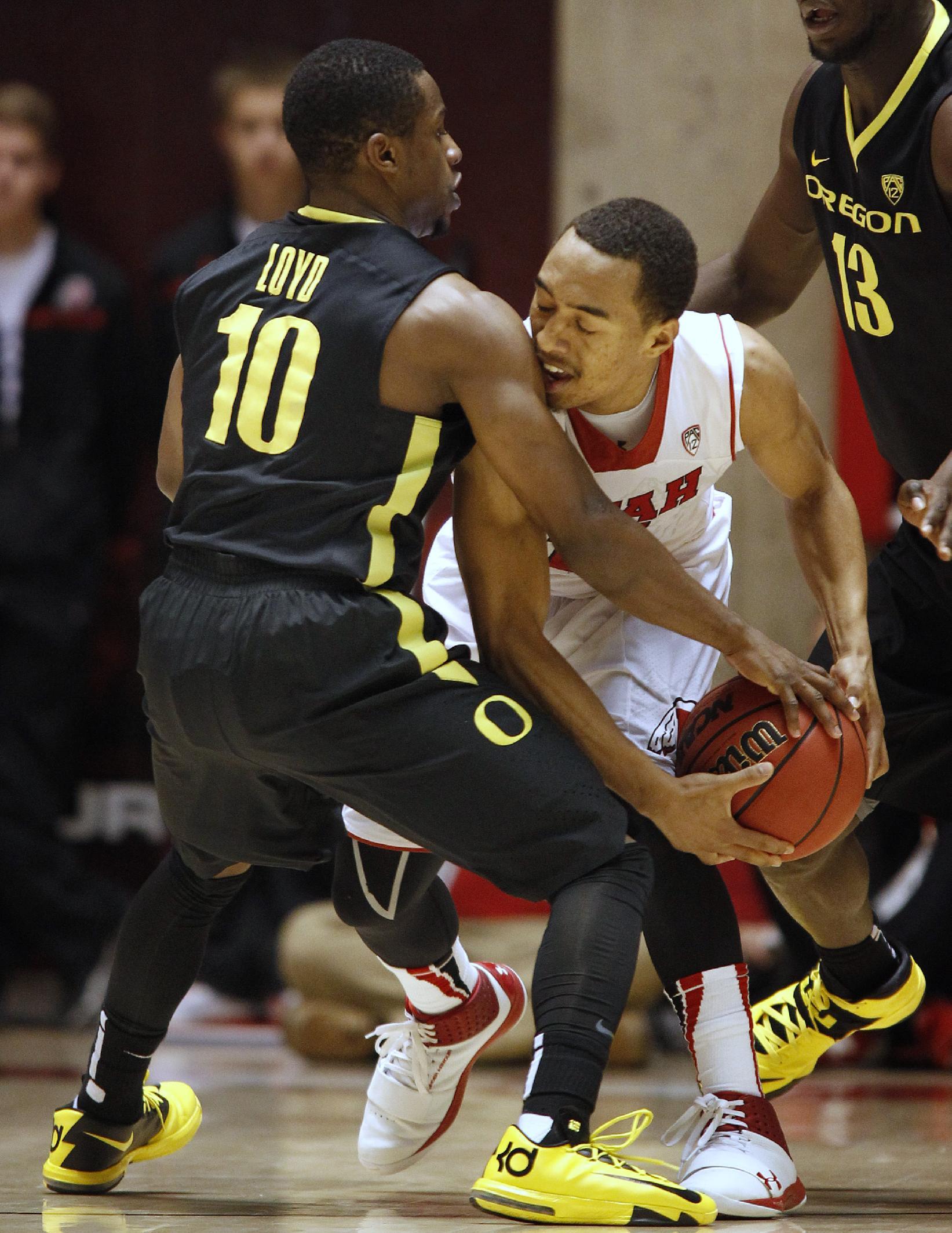 Oregon's Jonathan Loyd, left, reaches in to defend Utah's Brandon Taylor during an NCAA college basketball game in Salt Lake City, Thursday, Jan. 2, 2014. Oregon beat Utah in overtime, 70-68