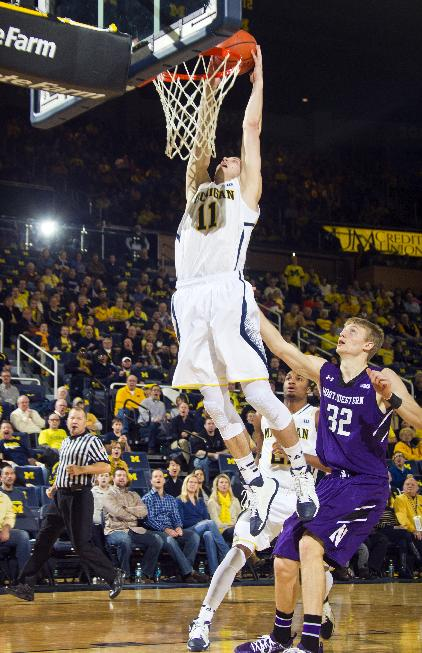 Michigan guard Nik Stauskas (11) dunks the ball while trailed by Northwestern forward Nathan Taphorn (32) in the first half of an NCAA college basketball game at Crisler Center in Ann Arbor, Mich., Sunday, Jan. 5, 2014