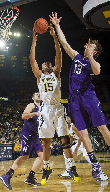 Michigan forward Jon Horford (15) and Northwestern forward Kale Abrahamson (13) compete for a rebound in the second half of an NCAA college basketball game in Ann Arbor, Mich., Sunday, Jan. 5, 2014. Michigan won 74-51