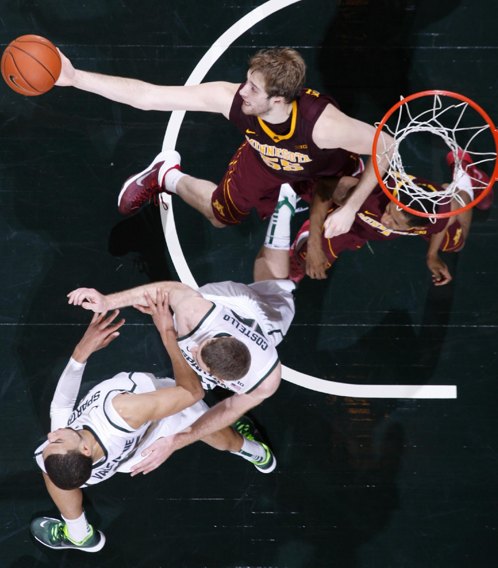 Minnesota's Elliot Eliason, top, pulls in a rebound against Michigan State's Matt Costello, center, and Denzel Valentine, bottom, during the second half of an NCAA college basketball game, Saturday, Jan. 11, 2014, in East Lansing, Mich. Michigan State won 87-75 in overtime