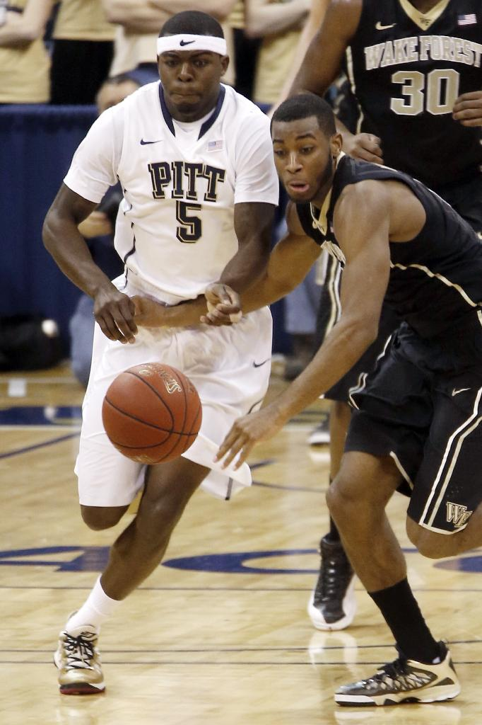 In this photo from Saturday, Jan. 11, 2014, Pittsburgh's Durand Johnson (5) chases after a loose ball with Wake Forest's Codi Miller-McIntyre in the NCAA college basketball game in Pittsburgh. Johnson will miss the rest of the season after tearing the ACL and meniscus in the game. He is expected to undergo surgery within the next week and to be back in 9 to 12 months