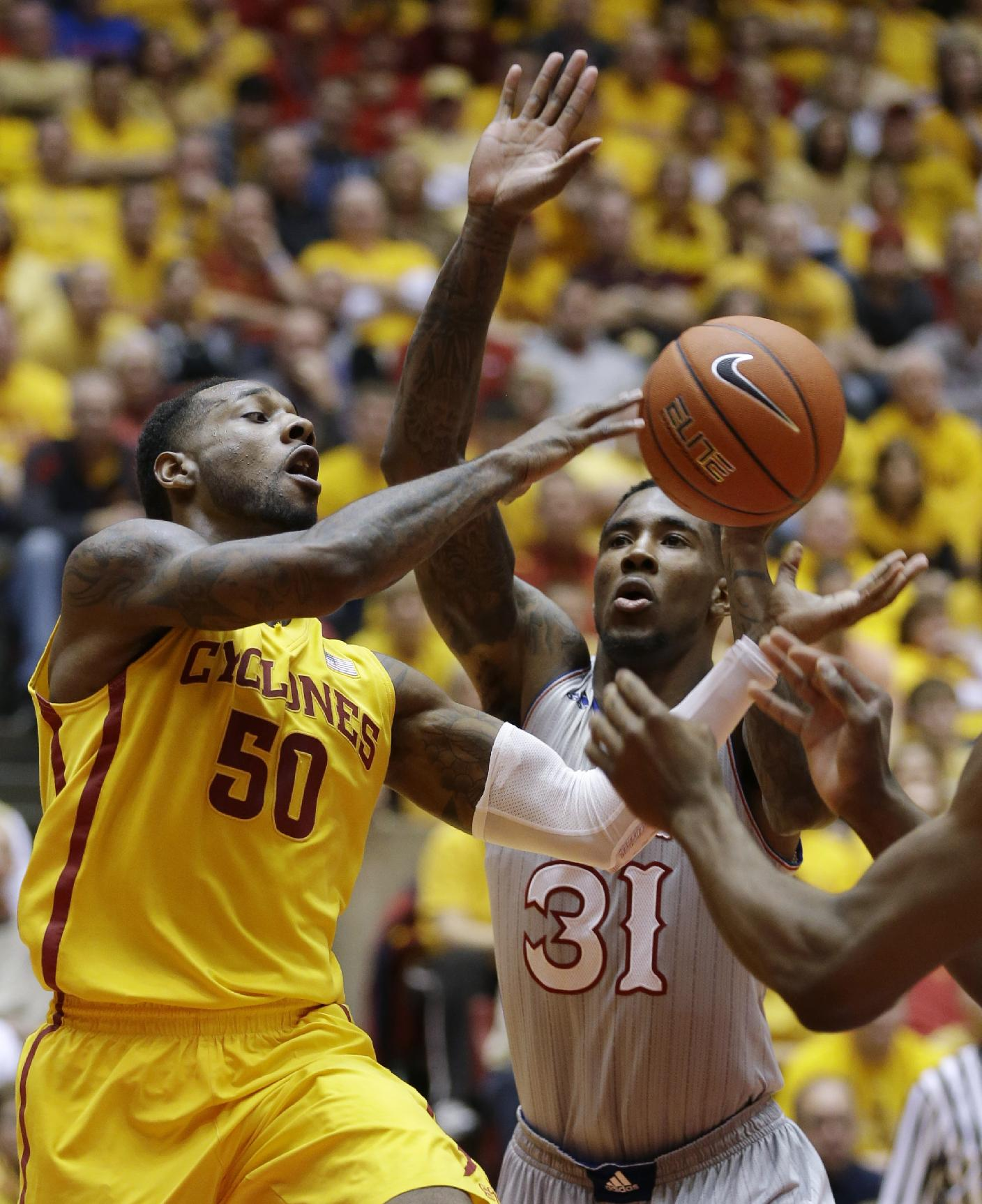 Iowa State guard DeAndre Kane (50) fights for a rebound with Kansas forward Jamari Traylor (31) during the first half of an NCAA college basketball game, Monday, Jan. 13, 2014, in Ames, Iowa