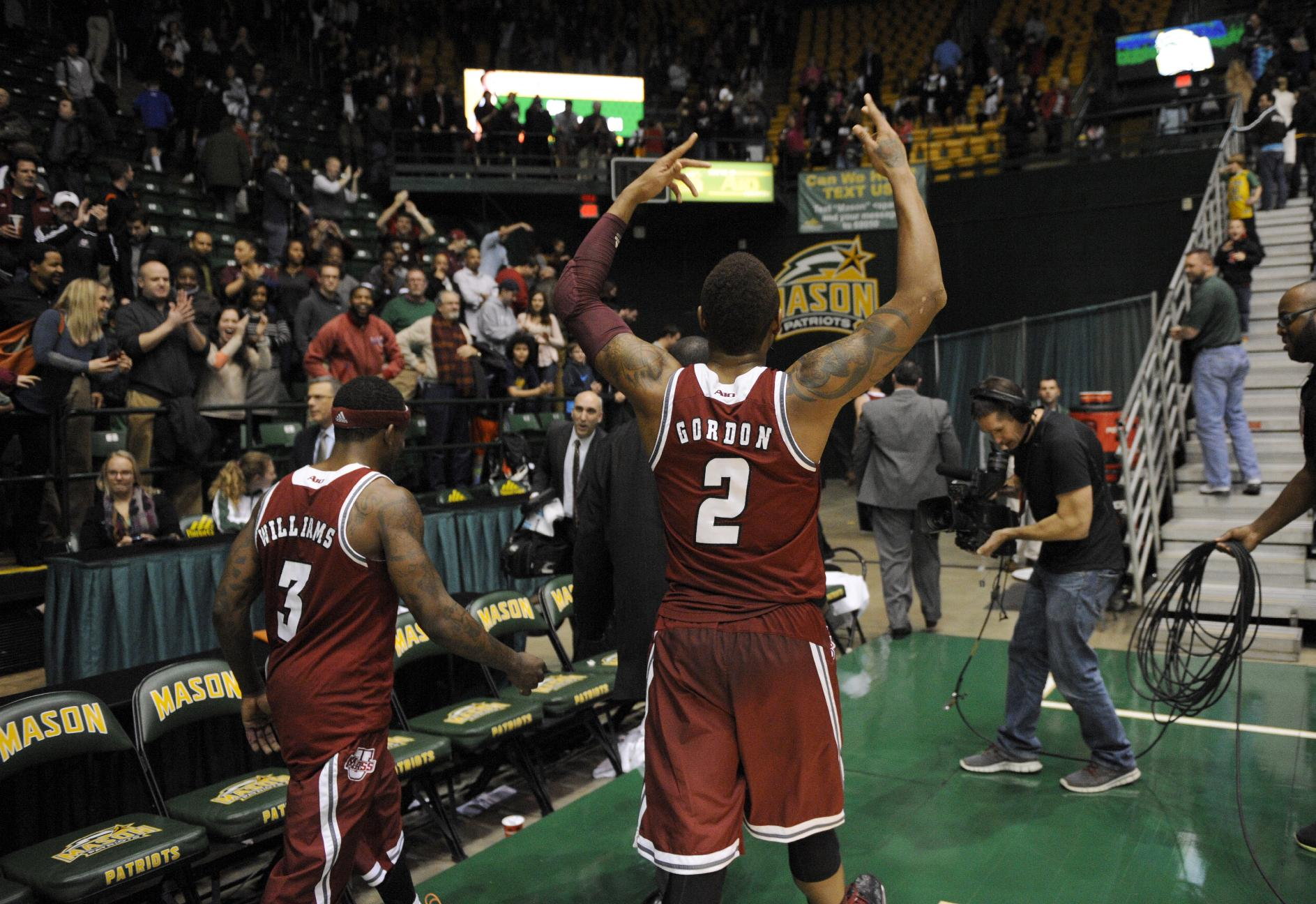 Massachusetts guard Derrick Gordon (2) raises his arms to the crowd as he and Chaz Williams (3) heads off the court after they beat George Mason 88-87 in an NCAA college basketball game, Wednesday, Jan. 15, 2014, in Fairfax, Va