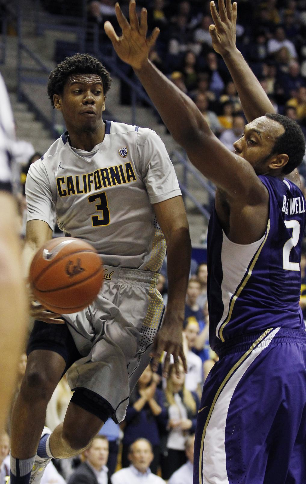 California's Tyrone Wallace (3) passes in front of Washington's Perris Blackwell during the second half of an NCAA college basketball game, Wednesday, Jan. 15, 2014, in Berkeley, Calif