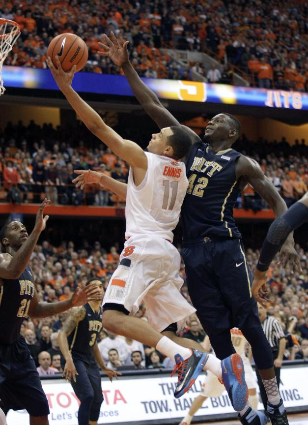 Syracuse's Tyler Ennis (11) shoots as Pittsburgh's Talib Zanna, right, defends during the second half of an NCAA college basketball game in Syracuse, N.Y., Saturday, Jan. 18, 2014. Syracuse won 59-54