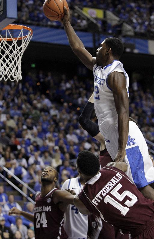 Kentucky's Alex Poythress, top, dunks over Texas A&M's Davonte Fitzgerald (15) and Antwan Space (24) during the second half of an NCAA college basketball game, Tuesday, Jan. 21, 2014, in Lexington, Ky. Kentucky won 68-51