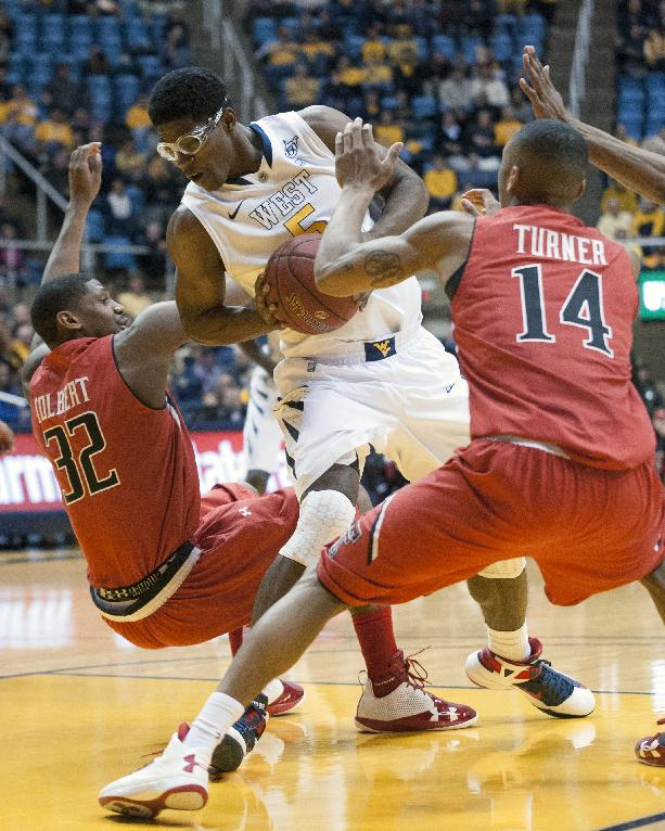 West Virginia's Devin Williams, middle, drives by Texas Tech's Jordan Tolbert (32) and Robert Turner (14) during the second half of an NCAA college basketball game Wednesday, Jan. 22, 2014, in Morgantown, W.Va. West Virginia won 87-81