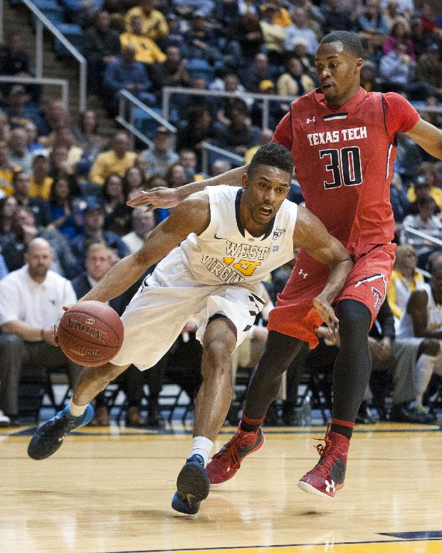 West Virginia's Terry Henderson, left, drives past Texas Tech's Jaye Crockett during the second half of an NCAA college basketball game Wednesday, Jan. 22, 2014, in Morgantown, W.Va. West Virginia won 87-81