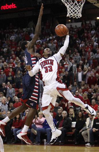 Deville Smith of UNLV gets blocked by Alex Davis of Fresno State during their NCAA basketball game at the Thomas & Mack Center in Las Vegas Saturday, Jan. 25, 2014