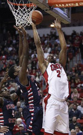 Khem Birch of UNLV goes up for a shot against Paul Watson of Fresno State during their NCAA basketball game at the Thomas & Mack Center in Las Vegas Saturday, Jan. 25, 2014