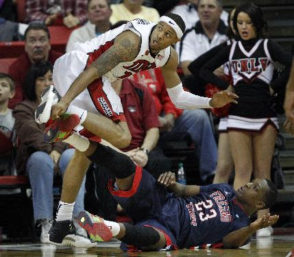 Bryce Dejean-Jones of UNLV falls onto Marvelle Harris of Fresno State during their NCAA basketball game at the Thomas & Mack Center in Las Vegas Saturday, Jan. 25, 2014