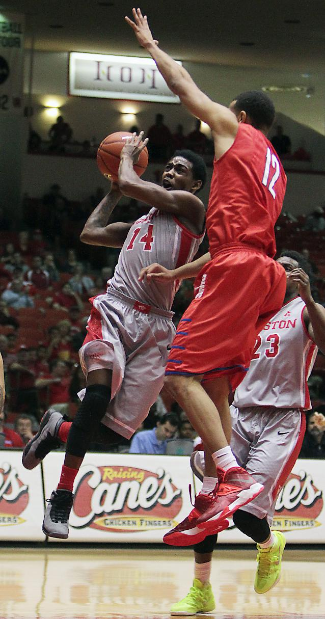Houston guard Tione Womack, left, goes for the basket as SMU's Nick Russell, right, defends during the first half of an NCAA college basketball game on Sunday, Jan. 26, 2014, in Houston