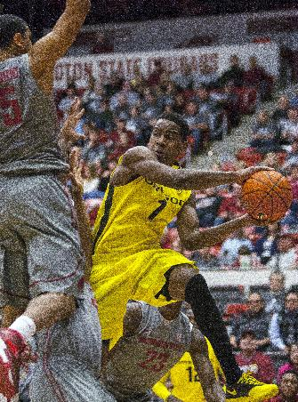 Oregon guard Dominic Artis (1) dishes a pass around Washington State guard Will DiIorio (5) after driving the baseline during the first half of an NCAA college basketball game Sunday, Jan. 26, 2014, in Pullman, Wash