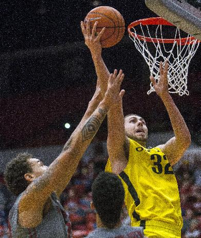 Oregon forward Ben Carter (32) scores while guarded by Washington State center Jordan Railey, left, during the first half of an NCAA college basketball game, Sunday, Jan. 26, 2014, in Pullman, Wash