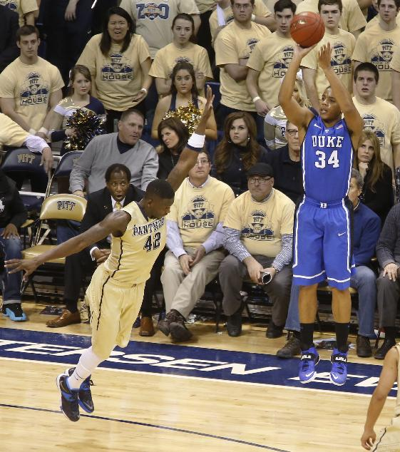 Duke's Andre Dawkins (34) hits a three-point shot over Pittsburgh's Talib Zanna (42) during the second half of an NCAA college basketball game on Monday, Jan. 27, 2014, in Pittsburgh. Duke won 80-65