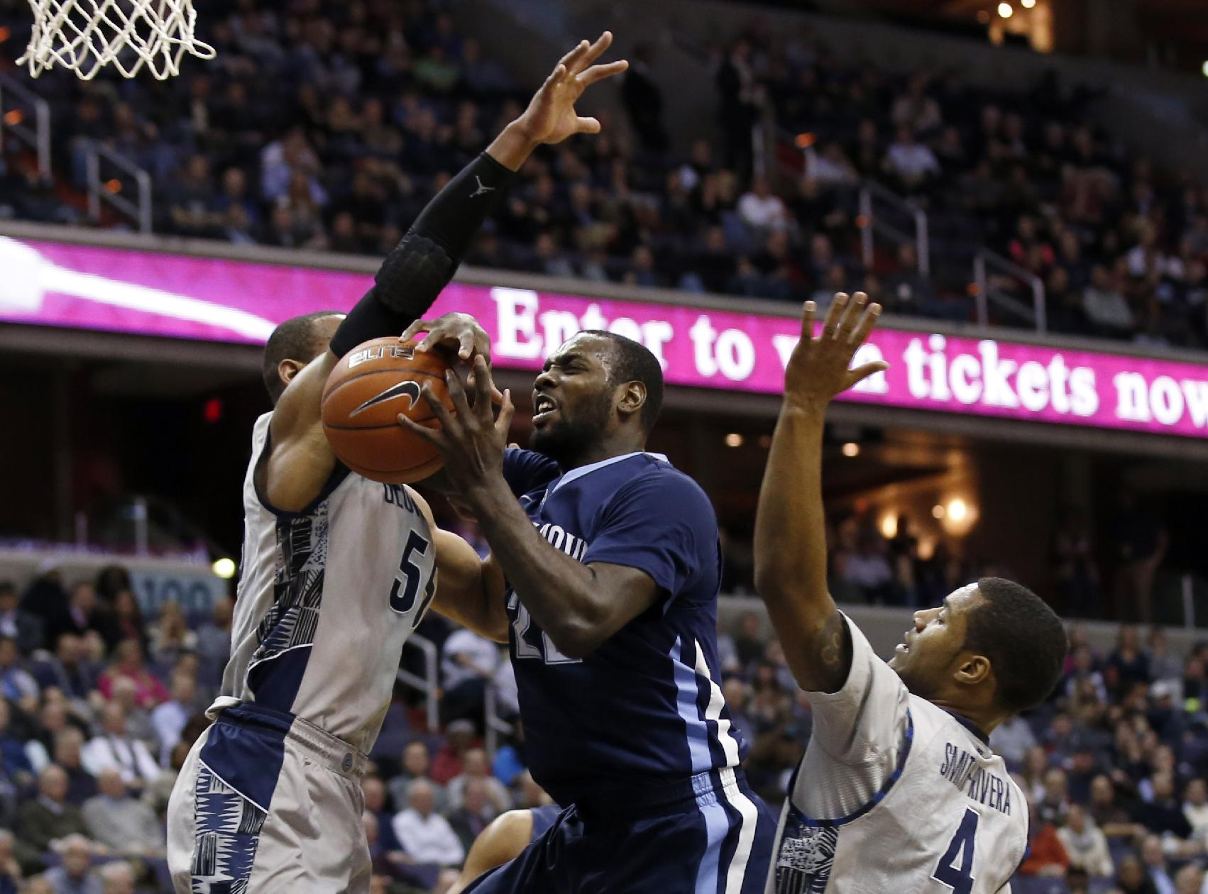 Villanova forward JayVaughn Pinkston (22) tries to shoot between Georgetown guards Jabril Trawick (55) and D'Vauntes Smith-Rivera (4) during the first half of an NCAA college basketball game, Monday, Jan. 27, 2014, in Washington