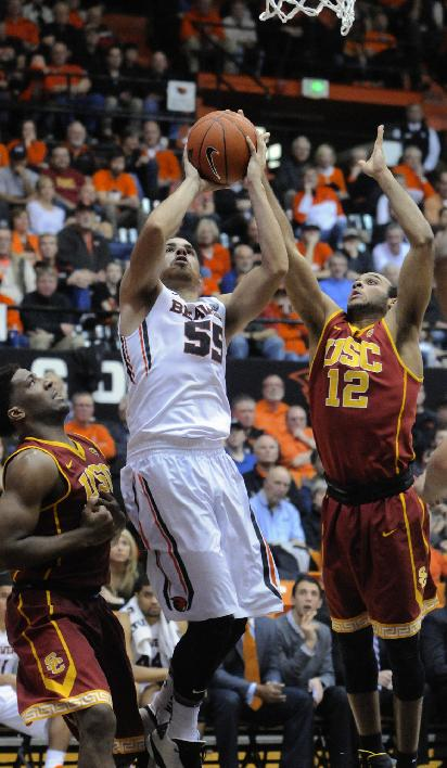 Oregon State's Roberto Nelson (55) shoots against USC's Pe'Shon Howard (10) and Julian Jacobs (12) during the second half of an NCAA college basketball game in Corvallis, Ore., Thursday Jan. 30, 2014. Nelson had 24 points as Oregon State beat USC 76-75 in overtime