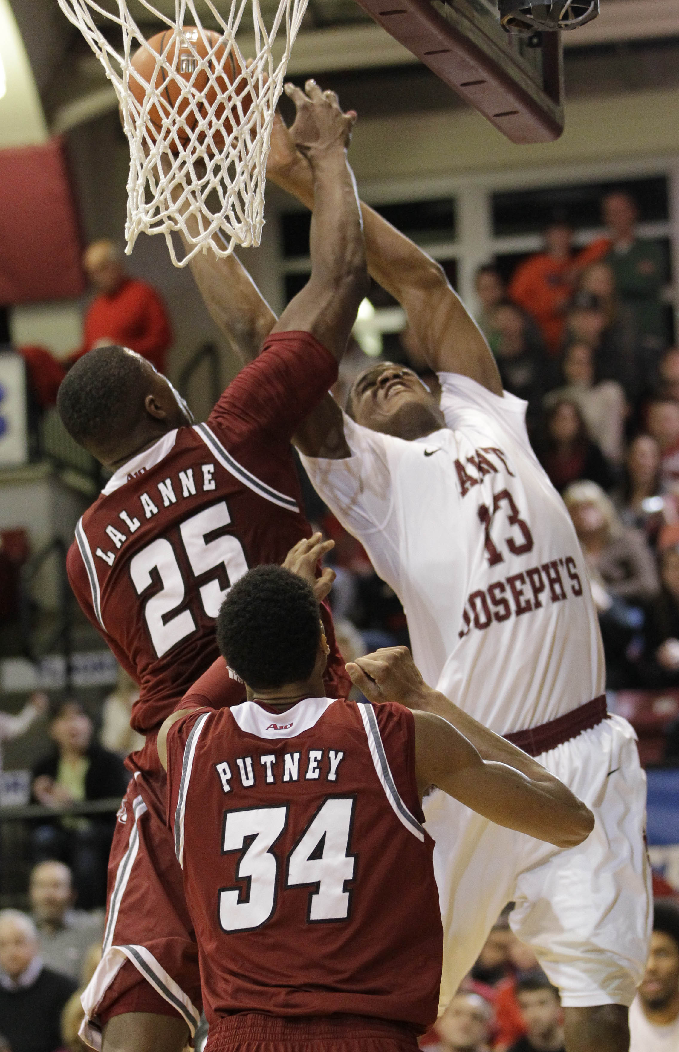 St. Josephs' Ronald Roberts Jr. (13) goes up for a basket past Massachusetts' Cady Lalanne (25) and Raphiael Putney (34) in the second half of an NCAA college basketball game, Saturday, Feb. 1, 2014, in Philadelphia.  St. Josephs won 73-68