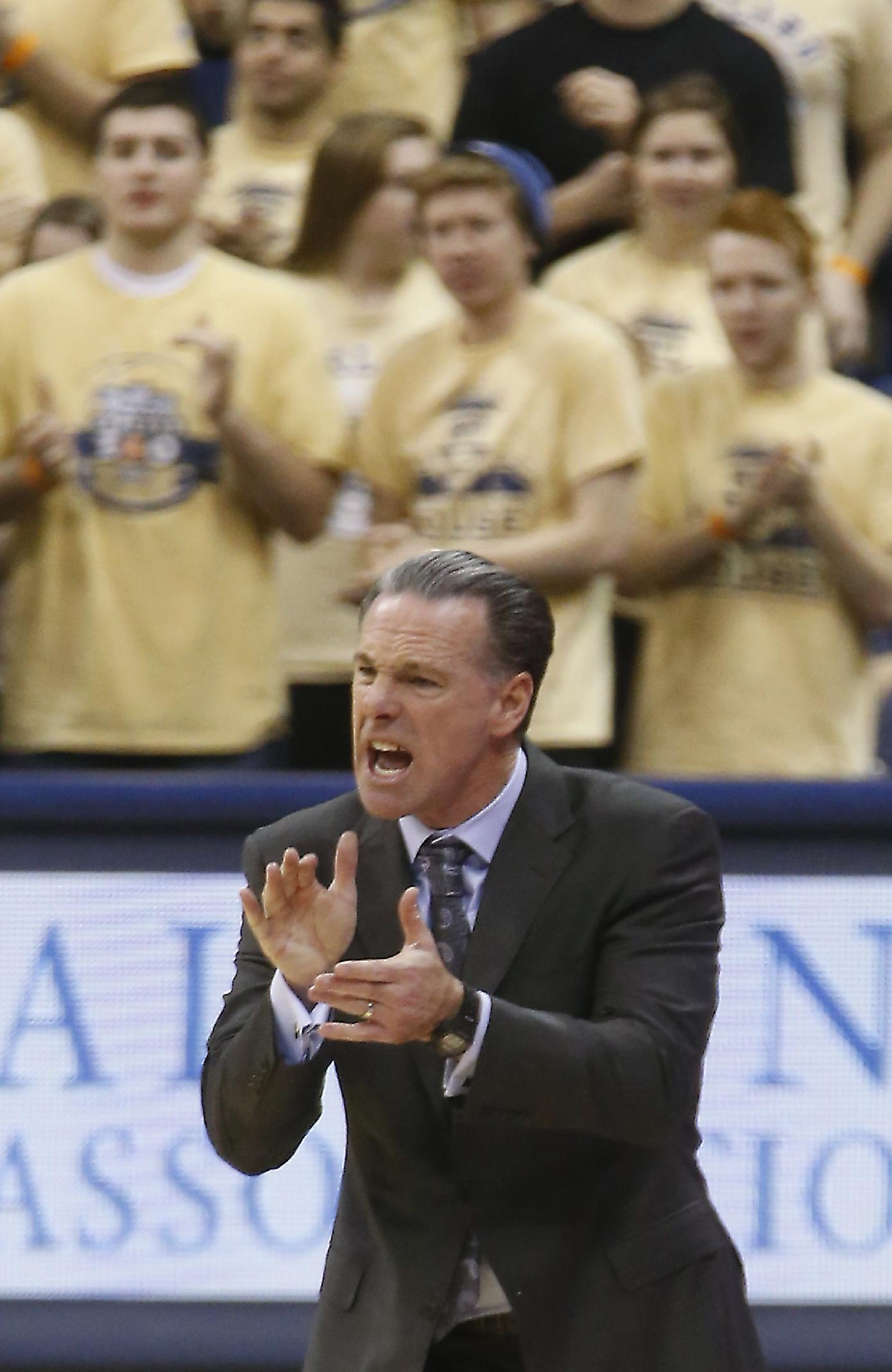 Pittsburgh head coach Jamie Dixon claps as he yells to his team during the first half of an NCAA college basketball game against Virginia Tech on Saturday, Feb. 8, 2014, in Pittsburgh. Pittsburgh won 62-57 in double overtime
