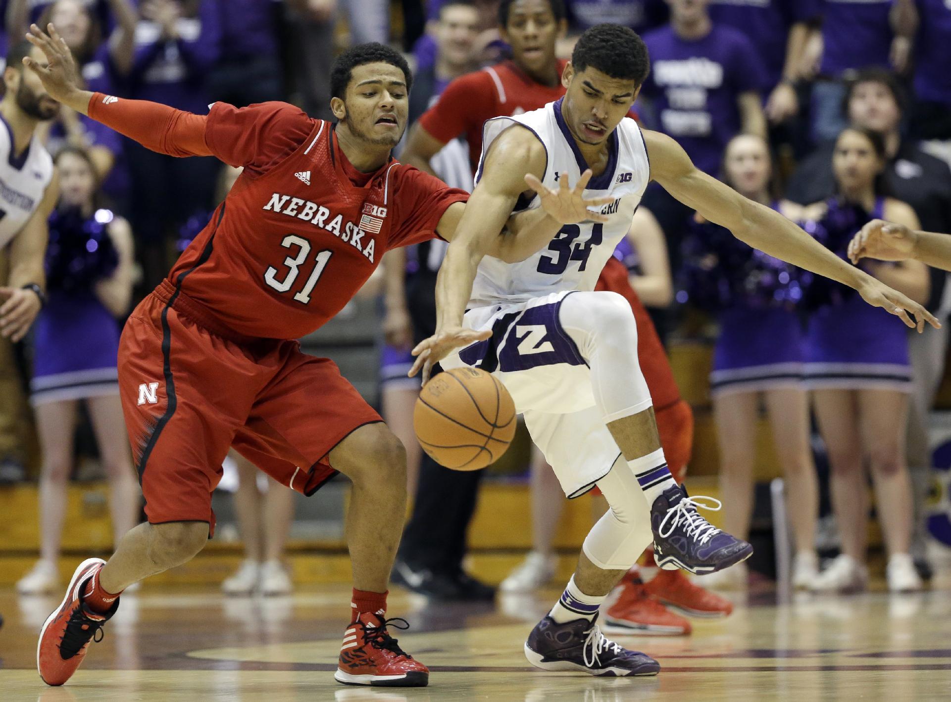 Northwestern guard Sanjay Lumpkin, right, and Nebraska guard Shavon Shields battle for a loose ball during the second half of an NCAA college basketball game in Evanston, Ill., on Saturday, Feb. 8, 2014. Nebraska won 53-49