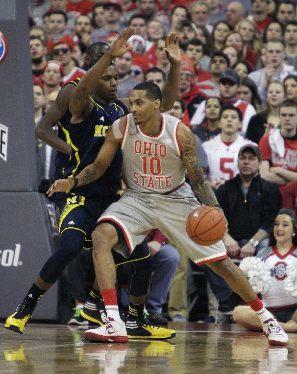 Ohio State's LaQuinton Ross, right, tries to get around Michigan's Glenn Robinson during the first half of an NCAA college basketball game, Tuesday, Feb. 11, 2014, in Columbus, Ohio