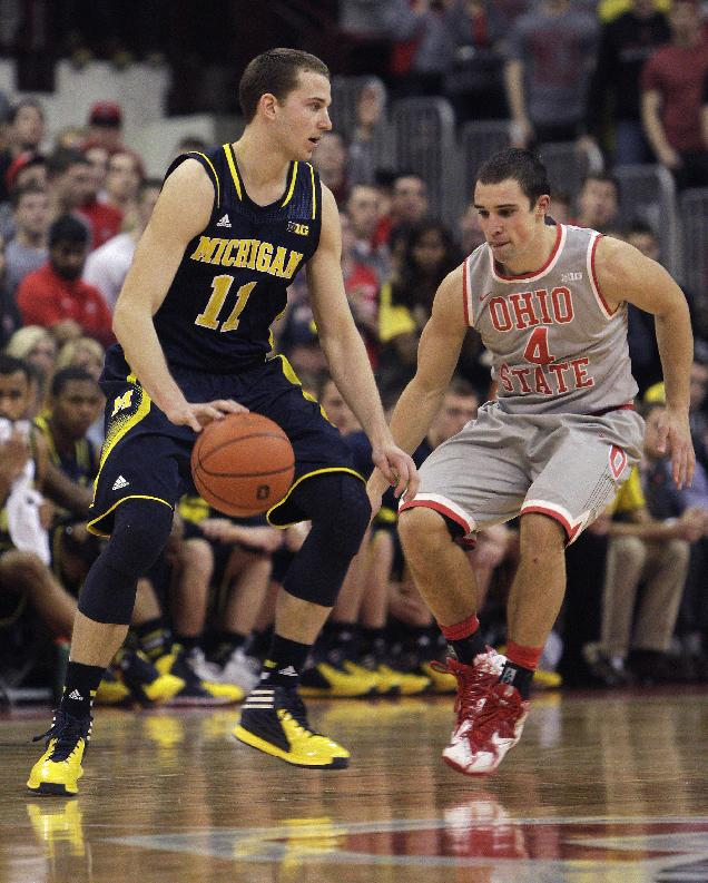 Michigan's Nik Stauskas, left, looks to pass as Ohio State's Aaron Craft defends during the second half of an NCAA college basketball game, Tuesday, Feb. 11, 2014, in Columbus, Ohio. Michigan won 70-60