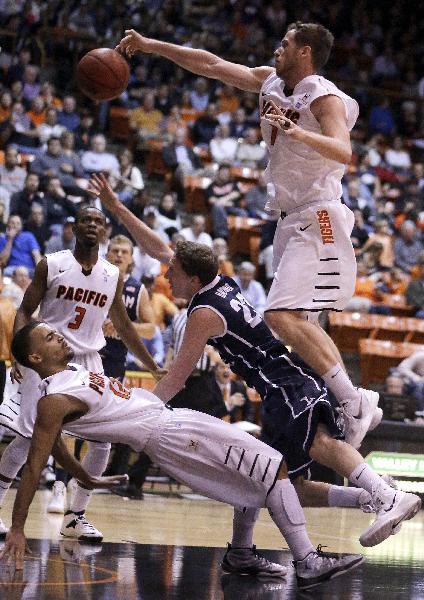 BYU's Skyler Halford (23) is fouled by Pacific's Trevin Harris, right, in the first half of an NCAA college basketball game Thursday, Feb. 13, 2014, in Stockton, Calif. Falling at left is Pacific's Andrew Bock (12)