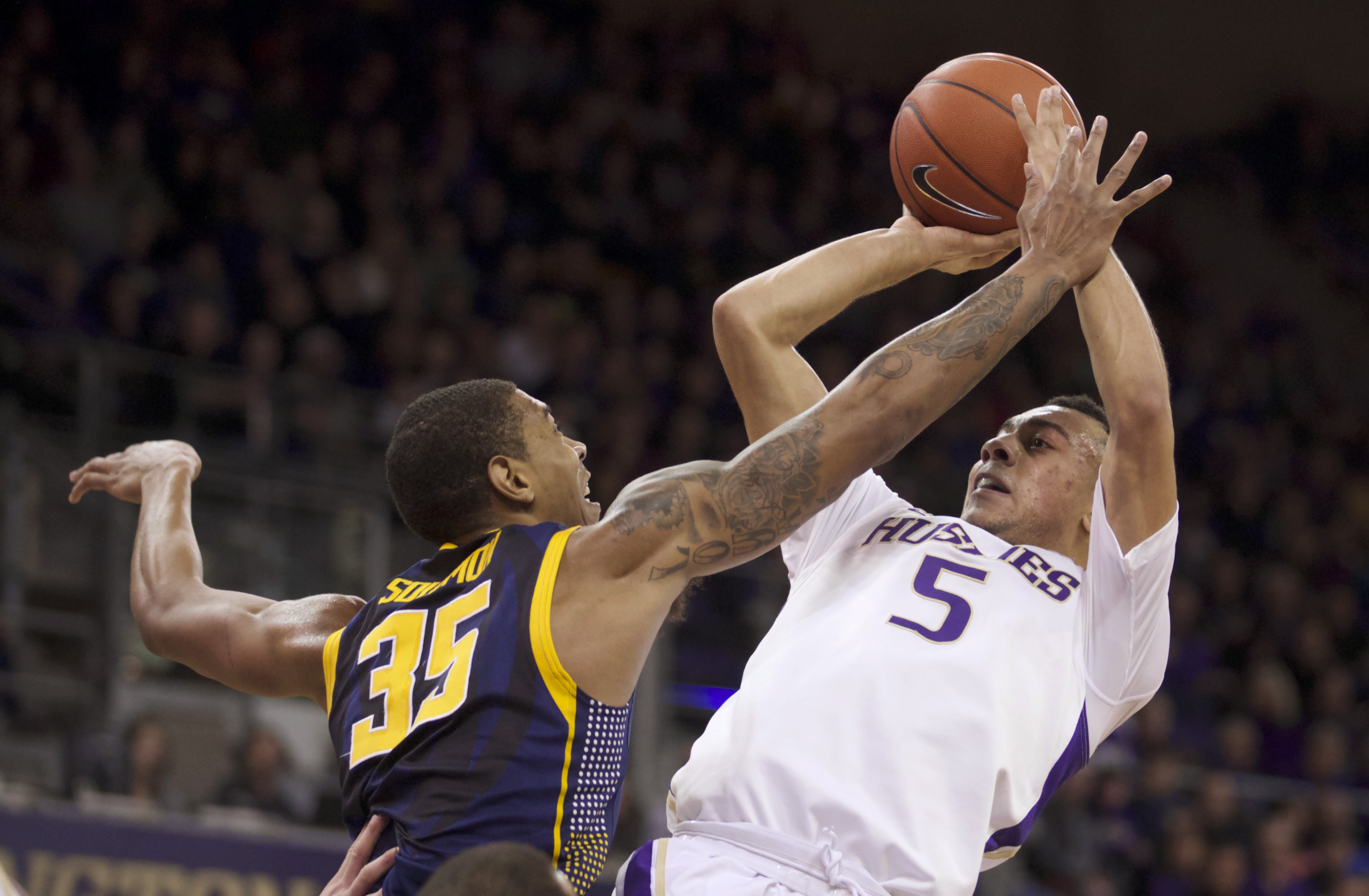 Washington's Nigel Williams-Goss, (5) attempts to shoot over California's Richard Solomon (35) in the first half of an NCAA college basketball game Saturday, Feb. 15, 2014