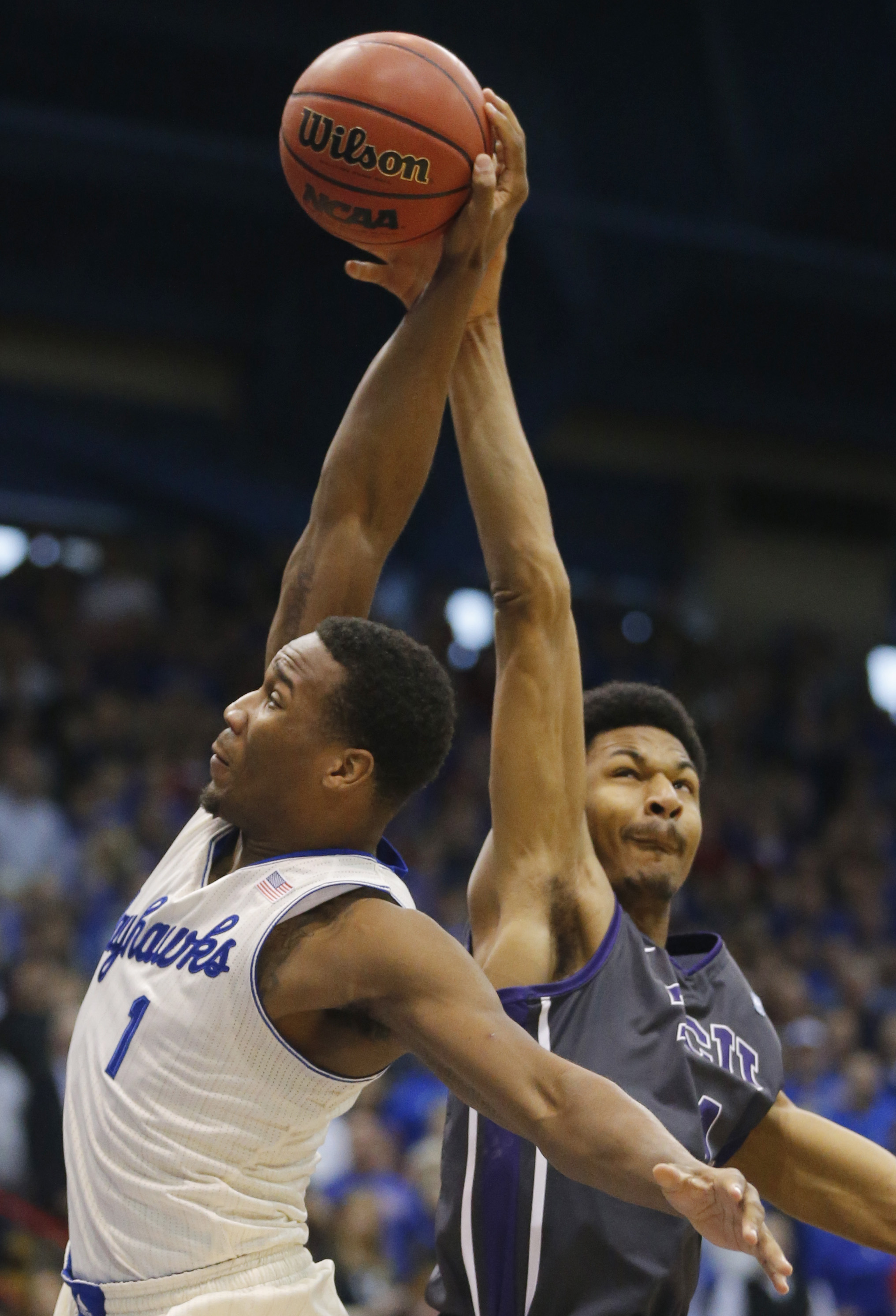 Kansas guard Wayne Selden Jr., left, is fouled by TCU center Karviar Shepherd, right, during the first half of an NCAA college basketball game in Lawrence, Kan., Saturday, Feb. 15, 2014