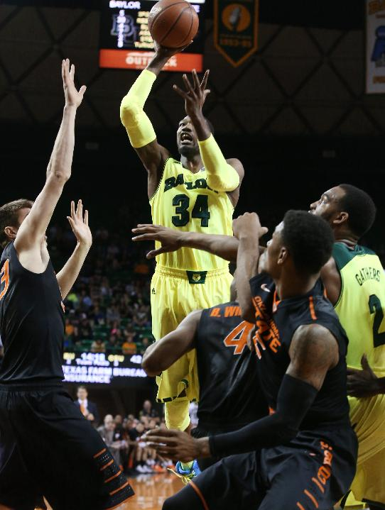 Baylor forward Cory Jefferson (34) scores past Oklahoma State forward/center Mason Cox (53), left, and other players in the second half of an NCAA college basketball game, Monday, Feb. 17, 2014, in Waco, Texas. Baylor won in overtime 70-64