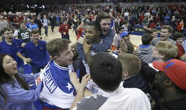 In this Feb. 8, 2014, file photo, SMU forward Markus Kennedy (5), center, is grabbed by students after an NCAA college basketball game against Cincinnati at Moody Coliseum in Dallas. Three decades after an unusual Dallas Mavericks' playoff game on the SMU campus spawned Moody Madness, the Mustangs are undefeated at home this season