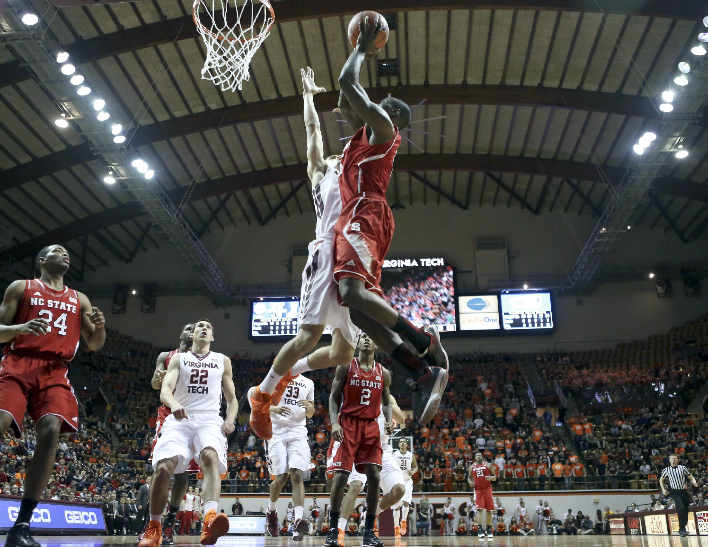 N.C. State's Desmond Lee, right, goes up for a shot against Virginia Tech's Devin Wilson during first half of an NCAA college basketball game in Blacksburg, Va., Saturday, Feb. 22 2014