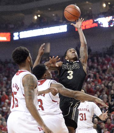 Purdue guard Ronnie Johnson (3) drives to the basket against Nebraska guard Benny Parker (3) and Nebraska guard Ray Gallegos (15) during the first half of an NCAA college basketball game in Lincoln, Neb., Sunday, Feb. 23, 2014