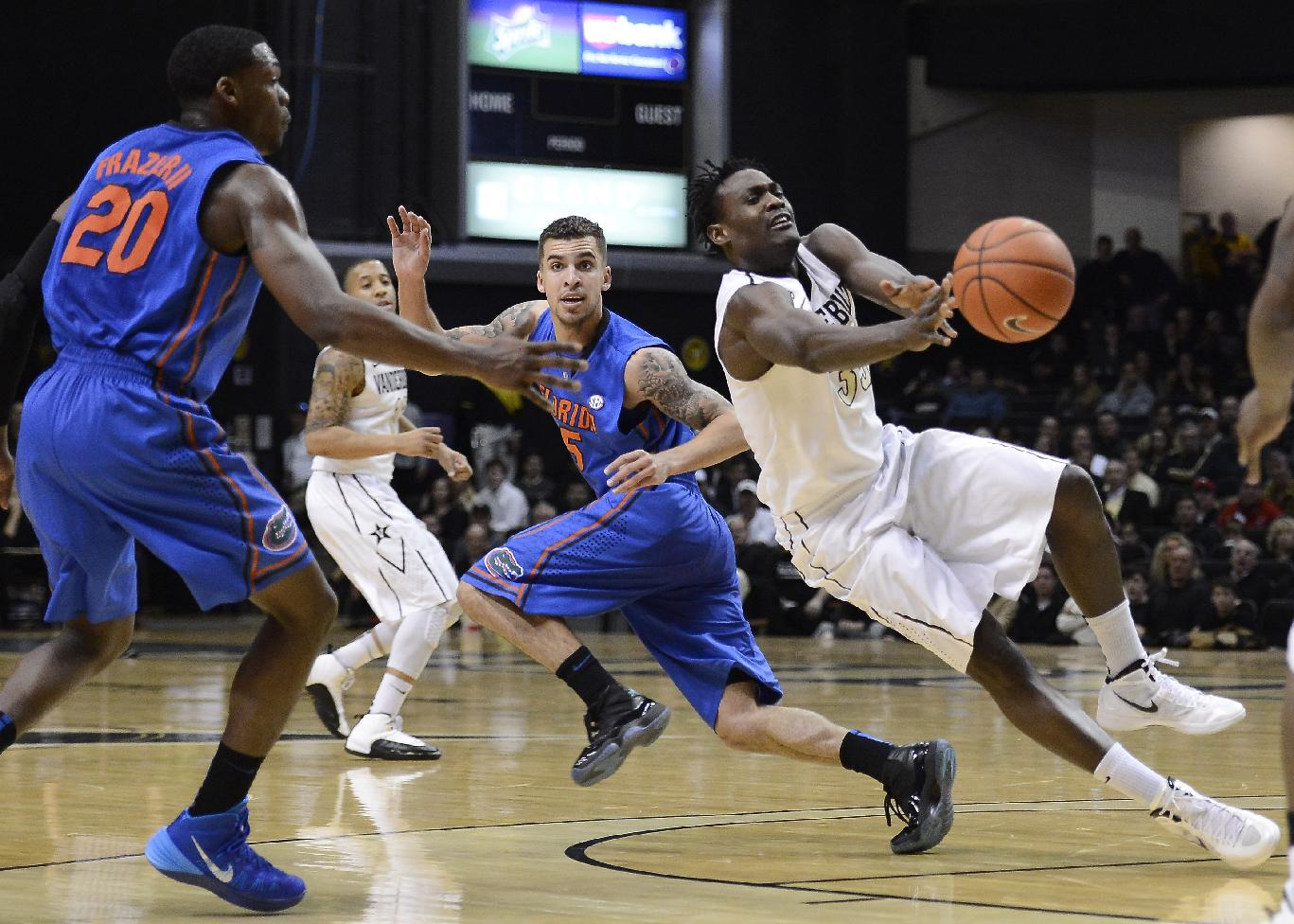 Vanderbilt forward James Siakam (35) passes the ball as he is defended by Florida guard Michael Frazier II (20) and guard Scottie Wilbekin (5) in the second half of an NCAA college basketball game, Tuesday, Feb. 25, 2014, in Nashville, Tenn. Florida won 57-54