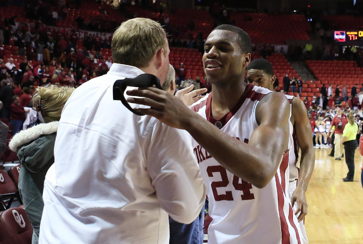 Oklahoma guard Buddy Hield (24) hugs a fan after Oklahoma defeated Texas in an NCAA college basketball game in Norman, Okla., Saturday, March 1, 2014. Oklahoma won 77-65