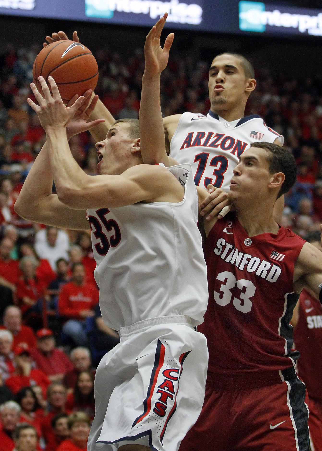 Arizona's Kaleb Tarczewski (35) and Nick Johnson (13) battle Stanford's Dwight Powell (33) for a rebound in the first half of an NCAA college basketball game, Sunday, March 2, 2014 in Tucson, Ariz